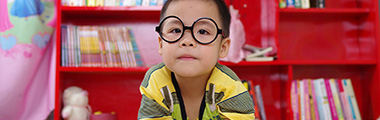 Young boy reading with glasses on